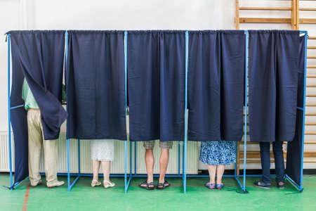 투표소에서 일부 투표 부스에서 투표하는 일부 사람들의 컬러 이미지. 스톡 콘텐츠