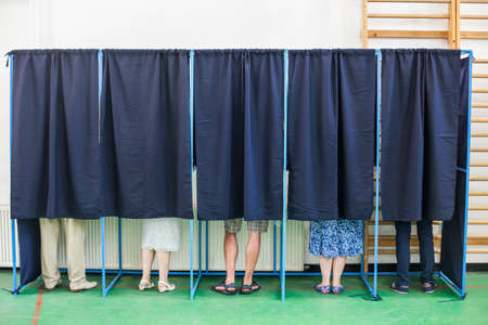 inserting: Color image of some people voting in some polling booths at a voting station. Stock Photo