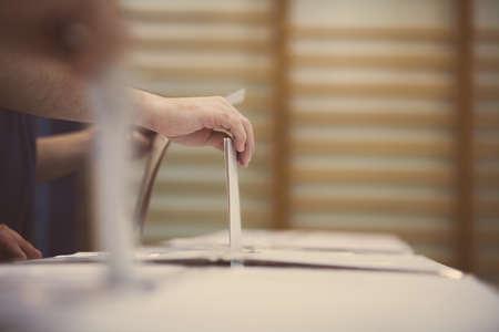 Hand einer Person wirft einen Stimmzettel in einem Wahllokal in Abstimmung. Standard-Bild - 58315452