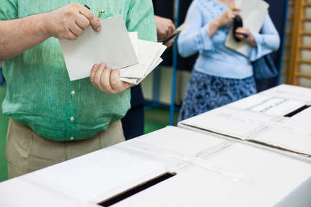 polling station: A person prepares to cast a ballot at a polling station during voting.