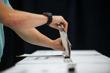 human arm: Hand of a person casting a ballot at a polling station during voting. Stock Photo