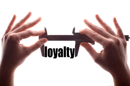 fidelity: Color horizontal shot of two hands holding a caliper and measuring the word loyalty.