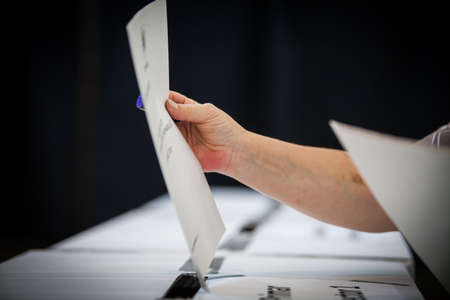 encuestando: La mano de una persona emitir su voto en un colegio electoral durante la votación.