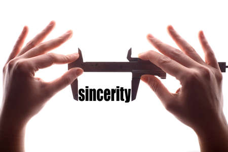 reliance: Color horizontal shot of two hands holding a caliper and measuring the word sincerity.