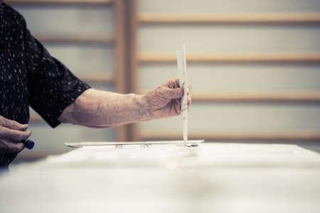 encuestando: La mano de una persona emitir su voto en un colegio electoral durante la votaci�n.