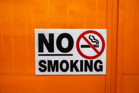 abstain: Color image of a no smoking sign on a wall. Stock Photo