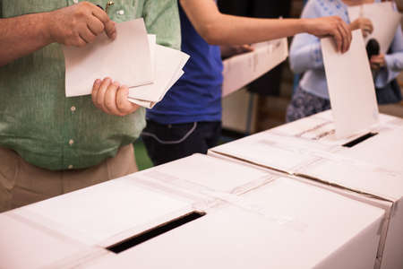 encuestando: Hand of a person casting a ballot at a polling station during voting. Foto de archivo