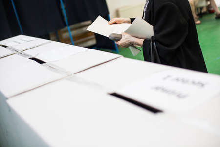 polling: A person prepares to cast a ballot at a polling station during voting.
