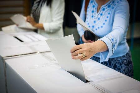 Hand einer Person wirft einen Stimmzettel in einem Wahllokal in Abstimmung. Standard-Bild - 61178388