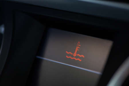 coolant: Close up shot of a cars electronic dashboard, with coolant warning on.