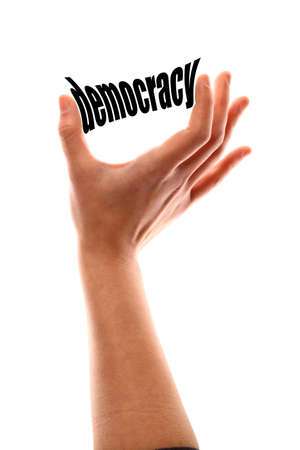 voting rights: Color vertical shot of a of a hand squeezing the word democracy. Stock Photo