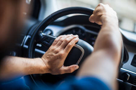honking: Close up shot of a mans hands holding a cars steering wheel and honking the horn.