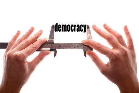 democracy: Color horizontal shot of two hands holding a caliper and measuring the word democracy.