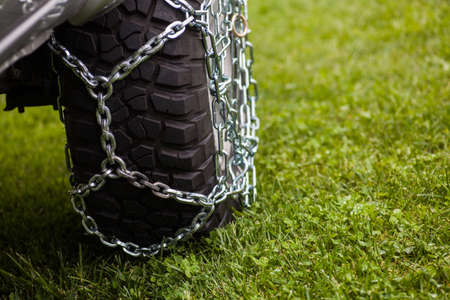 Close up shot of some chains wrapped around a cars tire.
