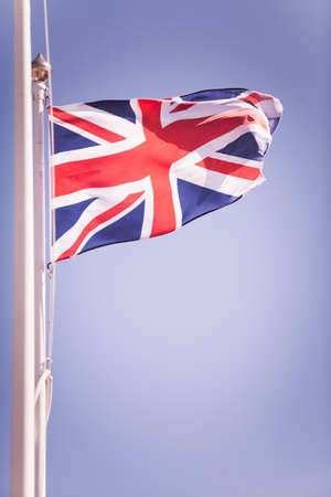 Color image of the United Kingdom flag, on cloudy background. Stock Photo