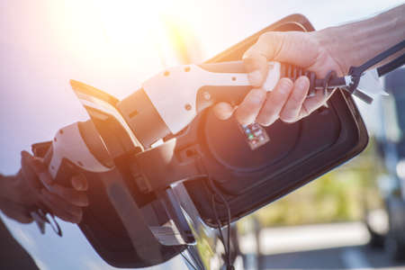 Color image of a mans hand preparing to charge an electric car. Stock Photo