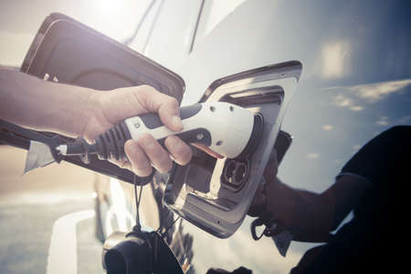 Color image of a man's hand preparing to charge an electric car.