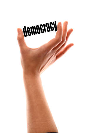 democracy: Color vertical shot of a of a hand squeezing the word democracy. Stock Photo