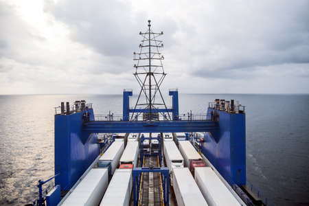 Color image of some trucks loaded on the deck of a ferry boat.