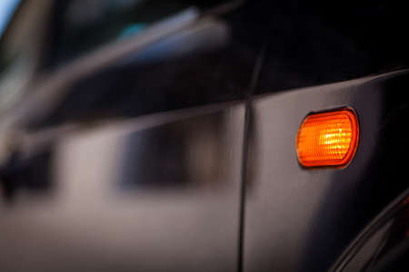 Color close up image of a cars turn signal blinking on the side.