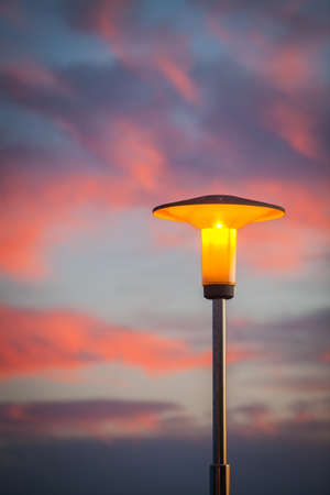 lit image: Color image of a lit street lamp, at sunset, with a background of pink clouds.