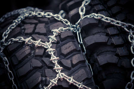 Close up shot of some snow chains installed on tires.