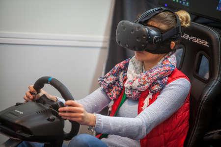Bucarest, Rumania - 26 de octubre de 2016: Una mujer está jugando un juego de conducción con engranaje de realidad virtual en. Editorial