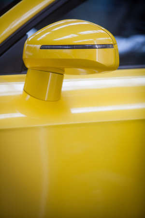 Color image of a yellow modern car side mirror.
