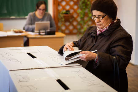 encuestando: Bucarest, Rumania - 11 diciembre 2016: Una mujer emite su voto durante la votación para las elecciones parlamentarias en un colegio electoral en Bucarest, Rumania. Editorial