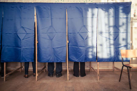 Die Menschen stimmen in einer Wahlkabine in einem Wahllokal. Standard-Bild - 68054649