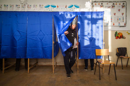 polling booth: Bucharest, Romania - December 11, 2016: A man exits a voting booth, during voting for parliamentary elections at a polling station in Bucharest, Romania. Editorial