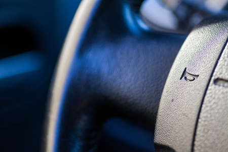 Close up shot of a cars horn button on the steering wheel.