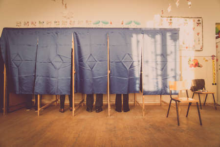 People vote in a voting booth at a polling station. Foto de archivo