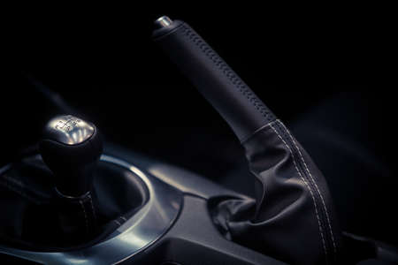 Close up shot of a parking brake lever and gear shifter inside a car. Stock Photo
