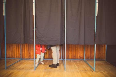 encuestando: La gente vota en una cabina de votación en un colegio electoral. Foto de archivo