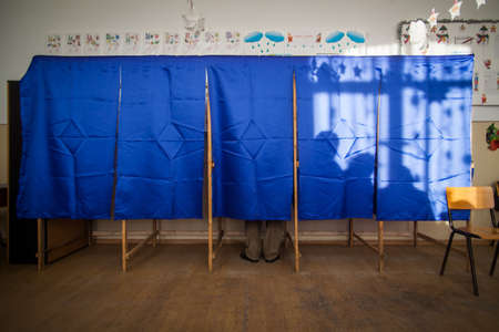 People vote in a voting booth at a polling station. Stock Photo