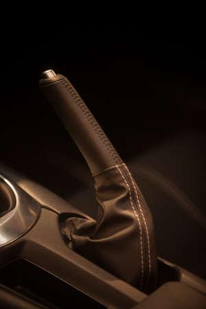 Close up shot of a parking brake lever inside a car.