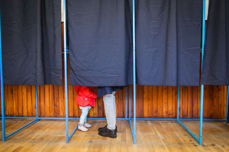 People vote in a voting booth at a polling station. Stockfoto