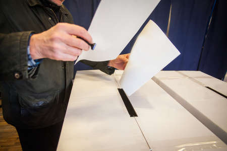 encuestando: A person casts her ballot during voting for parliamentary elections at a polling station in Bucharest, Romania.