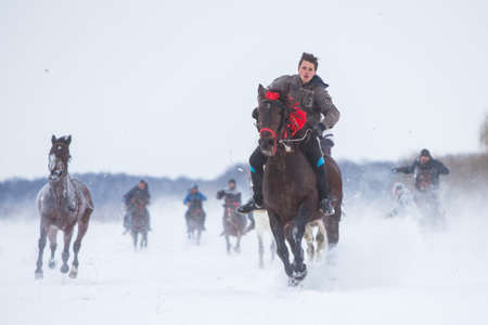 Pietrosani, Romania - January 6, 2017: People race their horses on a snowy field, during a traditional Epiphany horse race in Pietrosani, Romania. Редакционное