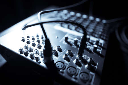 Close up shot of a mixer desk with many buttons and cables.