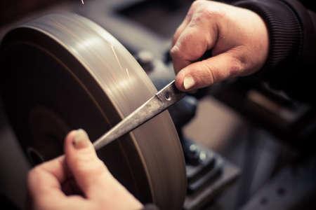 Close up shot of a mans hands sharpening a scissors.