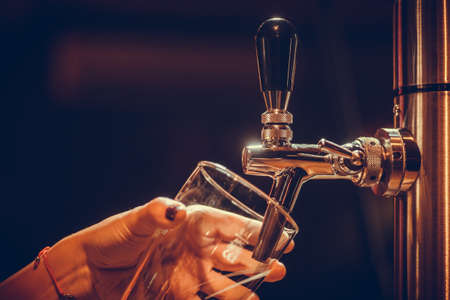 Image of a waiter pouring draught beer into a glass, in a pub or restaurant.