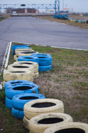 Yellow and blue tires on the floor of race course.