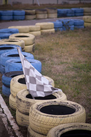 Race flag, yellow and blue tires on the floor of race course.