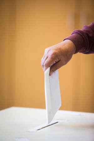 Color image of a person casting a ballot at a polling station, during elections. Stock fotó