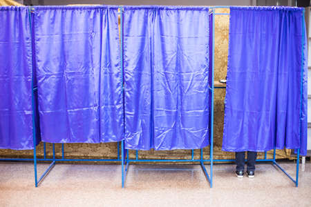 Color image of an unidentifiable person voting in booths at a polling station, during elections. Imagens