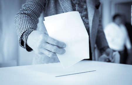 Color image of a person casting a ballot at a polling station, during elections. 免版税图像