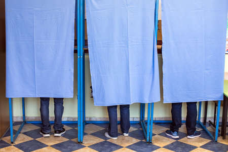 Color image of unidentifiable persons voting in booths at a polling station, during elections. Archivio Fotografico - 113556136