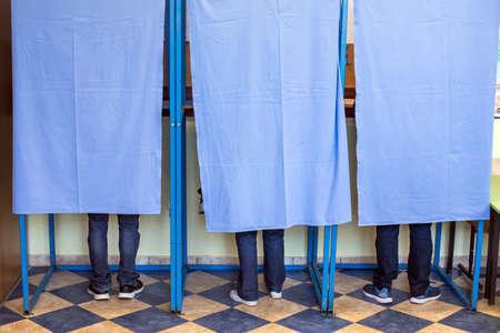 Kolorowy wizerunek niezidentyfikowanych osób głosujących w budkach w lokalu wyborczym, podczas wyborów.
